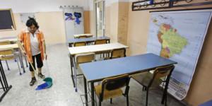 Una bidella pulisce un'aula il primo giorno di scuola al liceo Newton di Roma, oggi 12 settbre 2011 a Roma. ANSA/ALESSANDRO DI MEO